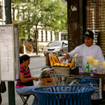 In a multi-cultural community like the Bronx, foods from residents' home countries become local favorites. In this picture, a vendor sells grilled corn and mangos on sticks – both popular street foods in Mexico.