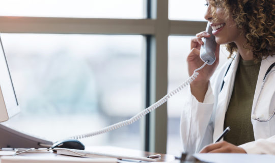 Cheerful, confident female doctor makes patient calls from office phone
